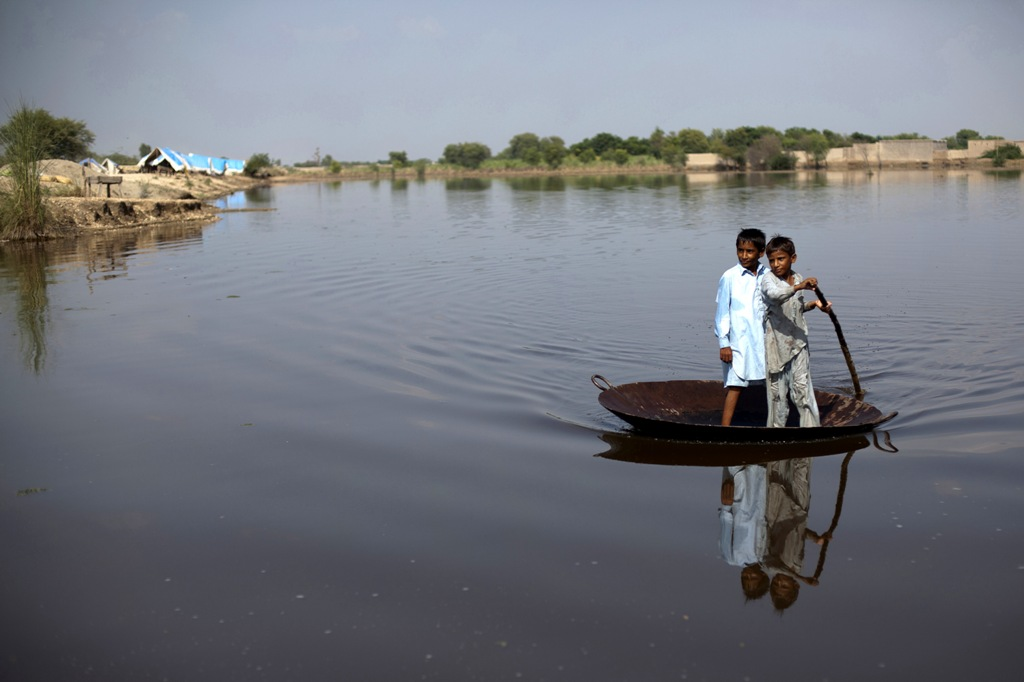 Boys use a large steel pot as a raft to cross an expanse of flood water in Pakistan. More than half a billion children across the world live in areas with extremely high flood risk. Photo: Unicef/2011/Zaidi